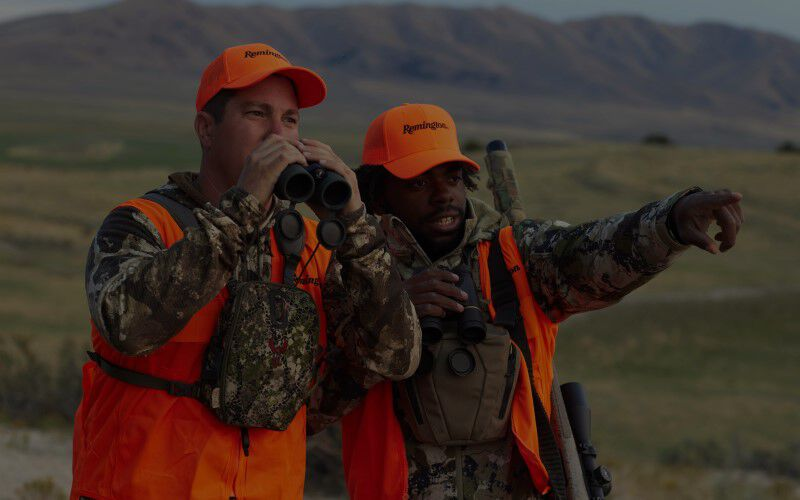 One hunter looking through binoculars and another hunter pointing to something in the field