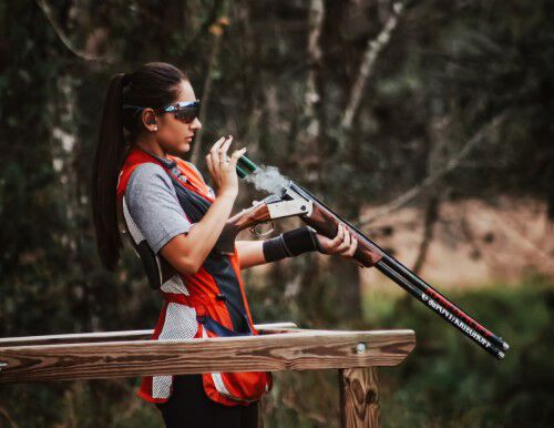 Reanna standing in competition apparel holding a shotgun