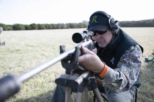 Ted Nugent looking down the scope of a rifle