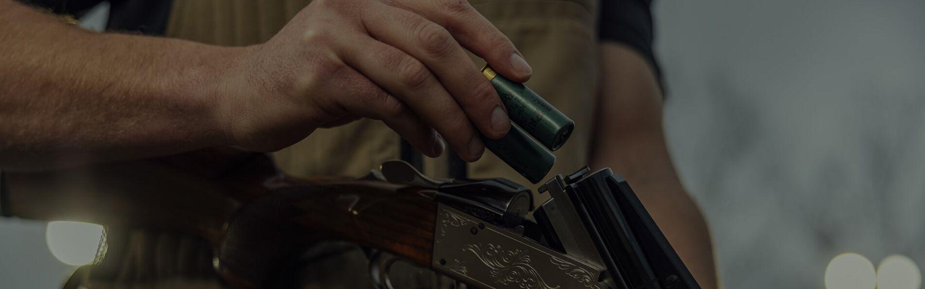 Shotshells being loaded into a shotgun